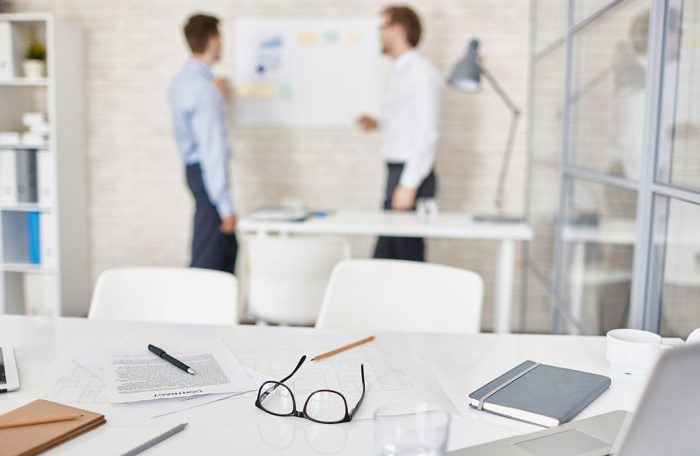 Empty workplace in office with businessmen interacting on background